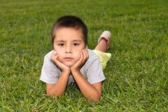 O menino sério encontra-se em uma grama Foto de Stock