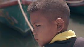 O menino sério no t-shirt amarelo preto olha em torno da pesca filme