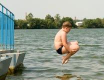 O menino salta foto de stock