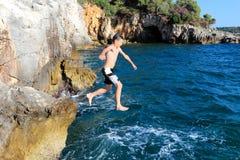 O menino salta do penhasco Imagem de Stock Royalty Free