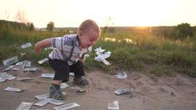 O menino salta felizmente em torno do dinheiro dispersado no movimento lento no por do sol filme
