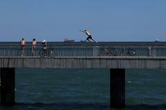 O menino salta na água da ponte divertimento no calor do verão Foto de Stock Royalty Free