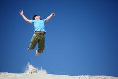 O menino salta na areia com mãos levantadas Fotografia de Stock