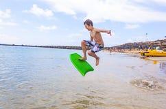 O menino salta no oceano com sua placa da dança Imagens de Stock Royalty Free