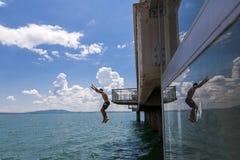 O menino saltado da ponte à água divertimento do verão no tempo quente Salte na água Fotos de Stock Royalty Free