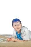 O menino senta-se em um background1 branco Imagem de Stock