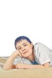O menino senta-se em um background2 branco Fotografia de Stock Royalty Free