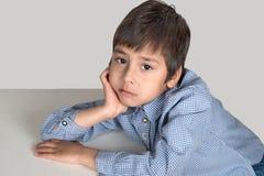 O menino senta-se em uma tabela e pensa-se Foto de Stock Royalty Free