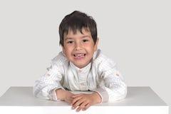 O menino senta-se em uma tabela e sorri-se Fotografia de Stock Royalty Free