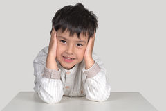 O menino senta-se em uma tabela e sorri-se Imagens de Stock Royalty Free