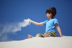 O menino senta-se na areia e dispersa-se a Fotos de Stock Royalty Free
