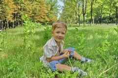 O menino senta-se na grama Fotografia de Stock