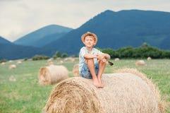 O menino senta-se na parte superior do monte de feno Fotos de Stock