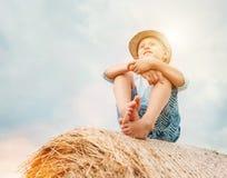 O menino senta-se na parte superior do monte de feno com fundo ensolarado do céu Imagem de Stock