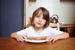 O menino senta-se na tabela de cozinha e não se quer comer Foto de Stock