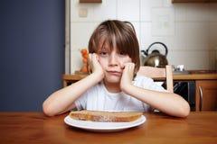 O menino senta-se na tabela de cozinha e não se quer comer Imagens de Stock Royalty Free