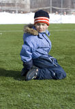 O menino senta-se no campo de futebol. Foto de Stock Royalty Free
