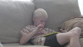O menino senta-se no sofá e nos jogos na tabuleta vídeos de arquivo