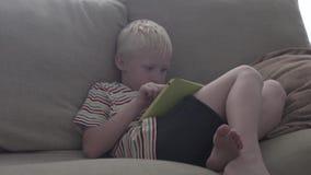 O menino senta-se no sof? e nos jogos na tabuleta vídeos de arquivo