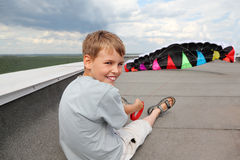 O menino senta-se no telhado da casa, prende o pára-quedas Fotos de Stock Royalty Free