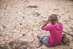 O menino sentou-se em uma terra estéril com desespero imagem de stock