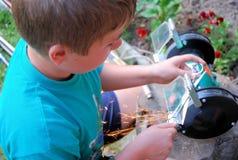 O menino sharpens ferramentas Foto de Stock