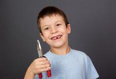 O menino simula a remoção do dente com alicates Fotografia de Stock Royalty Free