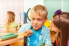 O menino surpreendido com olhos grandes senta-se na cadeira na mesa Fotos de Stock Royalty Free
