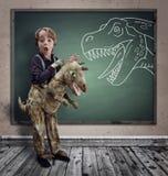 O menino surpreendido vestiu-se no vestido de fantasia como um dinossauro fotografia de stock royalty free