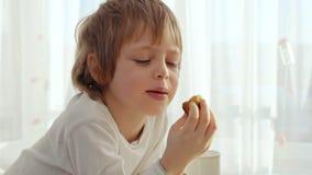 O menino tem o café da manhã na cozinha moderna O menino come a cookie com leite Tabela branca na cozinha Bacia na tabela