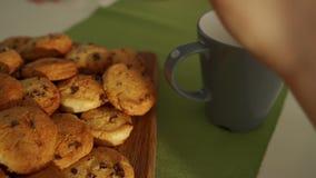 O menino tem o café da manhã na cozinha moderna O menino come a cookie com leite Tabela branca na cozinha Gray Bowl na tabela