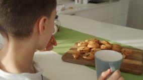 O menino tem o café da manhã na cozinha moderna O menino come a cookie com leite Tabela branca na cozinha Gray Bowl na tabela Fim