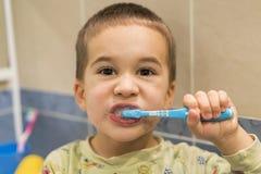 o menino tem escovado seus dentes no banheiro por 4 anos Close-up o rapaz pequeno escova os dentes em um banheiro imagem de stock royalty free