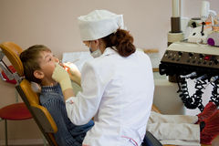O menino tem o dente periódico do exame no escritório médico imagens de stock royalty free