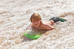 O menino tem o divertimento com a prancha Fotos de Stock Royalty Free