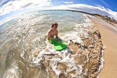 O menino tem o divertimento na praia Fotografia de Stock Royalty Free