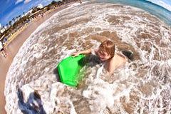 O menino tem o divertimento na praia foto de stock