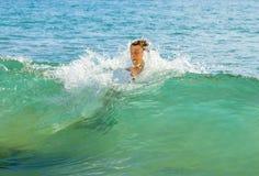 O menino tem o divertimento saltar nas ondas fotos de stock royalty free
