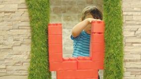 O menino tem três anos velho, jogos apenas na sala de crianças, está uma parede de grandes blocos plásticos video estoque