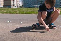O menino tira com giz azul no asfalto Mãos do close-up foto de stock