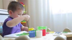 O menino tira com pinturas coloridas ao sentar-se na tabela filme