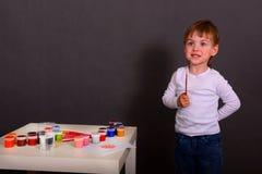 O menino tira pinturas coloridas fotografia de stock royalty free