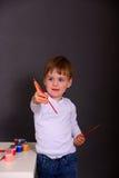 O menino tira pinturas coloridas imagem de stock royalty free