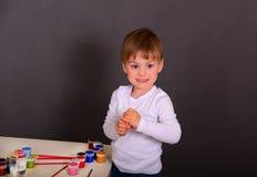 O menino tira pinturas coloridas imagens de stock royalty free