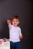 O menino tira pinturas coloridas fotos de stock