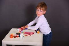 O menino tira pinturas coloridas foto de stock