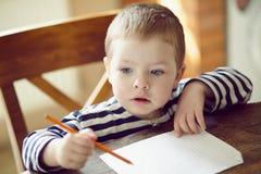 O menino tira. imagens de stock
