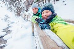 O menino toma a foto do auto com seu pai na caminhada do inverno na montanha Fotografia de Stock