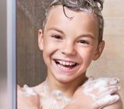 O menino toma um chuveiro no banheiro Fotos de Stock Royalty Free