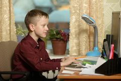 O menino trabalha em seu escritório em um computador pessoal Escreve o te Imagem de Stock Royalty Free